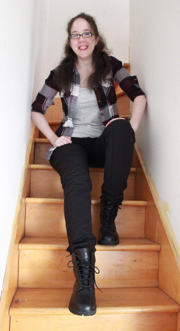 Photo of Claudie, sitting on the stairs and smiling at the camera.