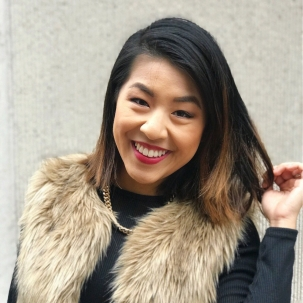 Close-up photograph of Joce, an Asian woman with shoulder-length black hair with brown highlights, smiling at the camera.