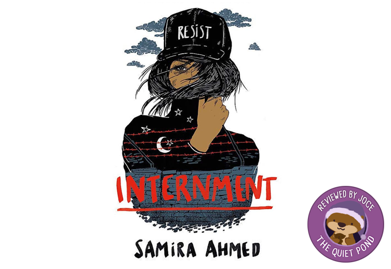 Text: Internment, Samira Ahmed. Image: A brown girl wearing a black cap with the word 'RESIST', her face partially concealed by her long hair. An illustration of a barbed wire stone fence is imposed on her shirt