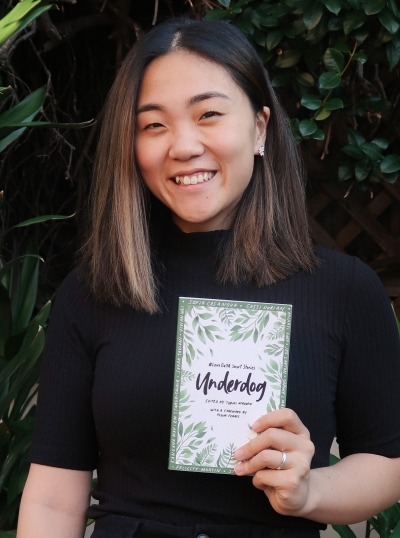 A photo of Vivian, holding up a book (Underdog edited by Tobias Madden), smiling at the camera.
