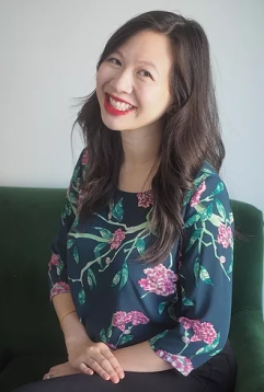 Photo of Elizabeth Lim, her hands folded at her lap, grinning at the camera.