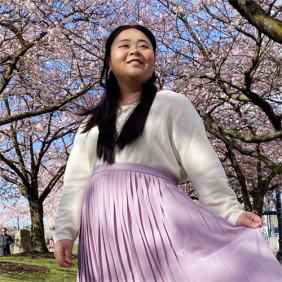 A photo of Lauren, wearing a white long-sleeve top and a lilac skirt, smiling and looking away from the camera.